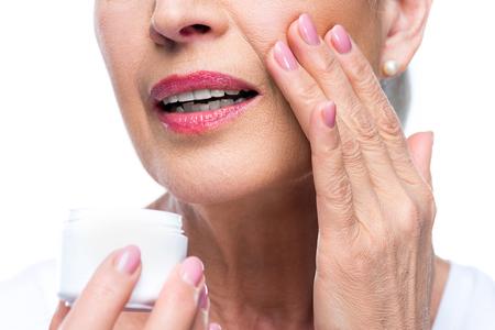 senior woman applying face cream Reklamní fotografie