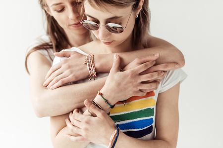 Woman hugging girlfriend from back