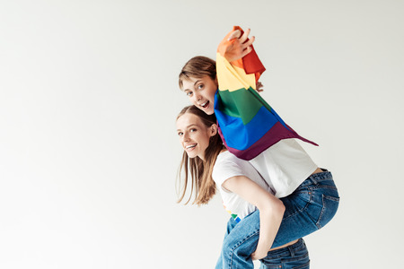 Woman giving piggyback to girlfriend with flag