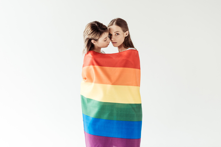 Lesbian couple wrapped in rainbow flag