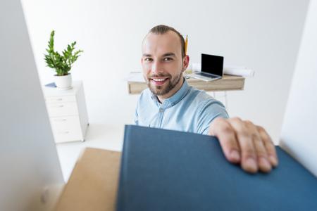 businessman reaching for paperwork on shelf Banco de Imagens