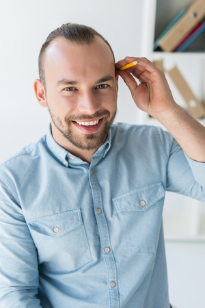 man with pencil behind ear Imagens