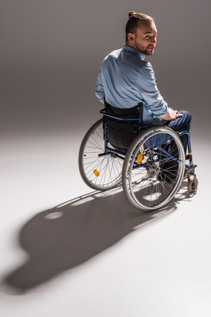 man on wheelchair casting shadow 스톡 콘텐츠