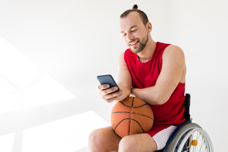 Disabled basketball player using smartphone