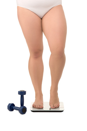 Fat woman on scales near dumbbells