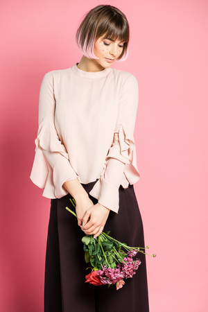 Trendy woman holding flowers