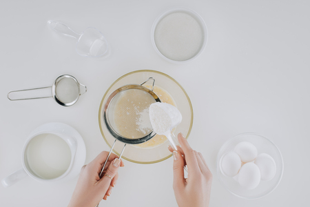 top view of person sifting flour while cooking pancakes isolated on grey