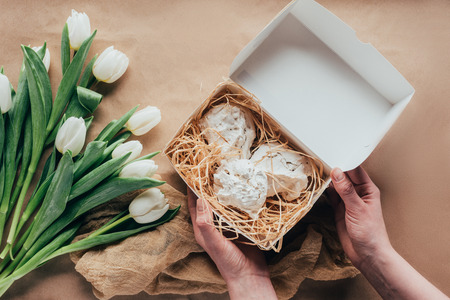 cropped shot of person holding box with delicious meringue cookies and white tulips 免版税图像