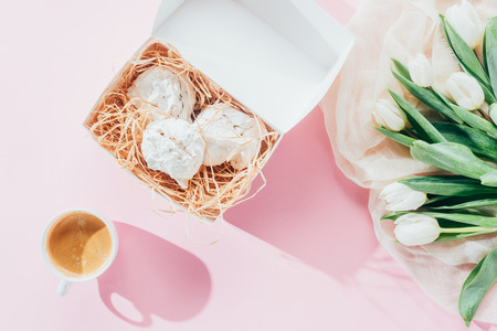 top view of white tulips, delicious meringue cookies and cup of coffee on pink