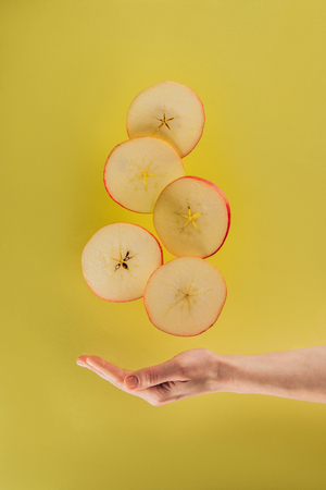 partial view of female hand and levitating pieces of apple
