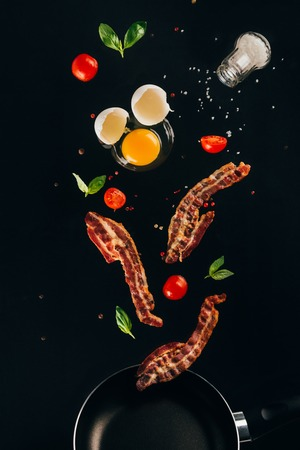 close up view of pieces of bacon, cherry tomatoes and raw egg yolk falling on frying pan isolated on black Stock Photo