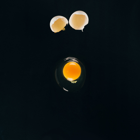 close up view of raw egg yolk falling on frying pan isolated on black Stock fotó - 95797150