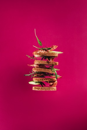 close up view of levitating sandwiches with bacon pieces and arugula isolated on pink