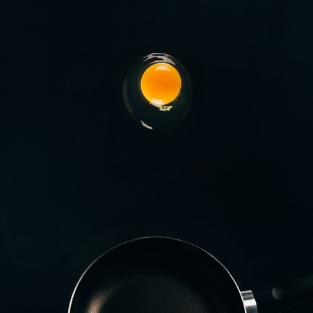 close up view of raw egg yolk falling on frying pan isolated on black Stock fotó