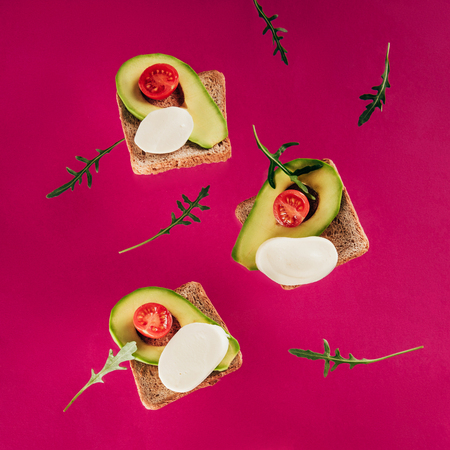 close up view of levitating toasts, pieces of avocado, cherry tomatoes, mozzarella cheese and arugula isolated on pink