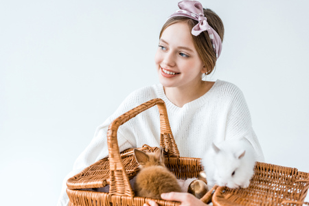 adorable happy girl holding basket with cute furry rabbits