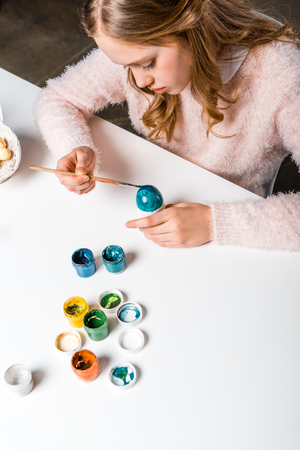 focused teenage girl painting easter egg at table