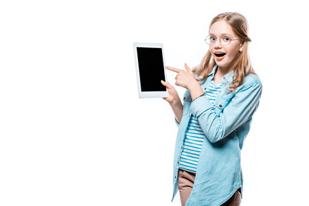 girl in eyeglasses pointing with finger at digital tablet with blank screen isolated on white