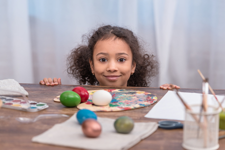 african american kid looking at camera near table with easter eggs
