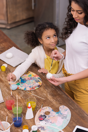 african american mother and daughter painting together easter eggs