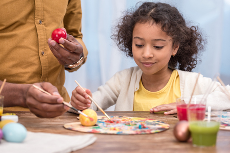 african american father and adorable daughter painting easter eggs with poster paints