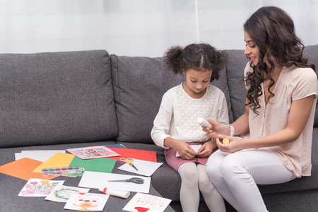 mother and daughter gluing paper for greeting card on mothers day