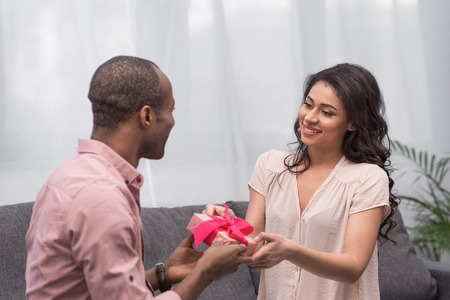 boyfriend presenting gift to girlfriend on international womens day Stock Photo