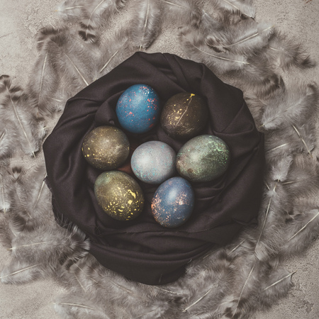 top view of shabby easter eggs in nest with feathers Reklamní fotografie
