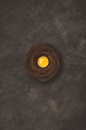 top view of broken egg with yolk in nest on concrete surface  Stockfoto