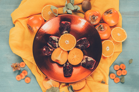top view of persimmons with oranges and pomegranates on plate on orange tablecloth