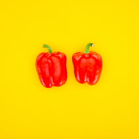 top view of fresh red paprika peppers isolated on yellow Stock Photo
