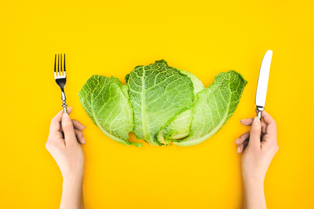 top view of person holding fork and knife while eating healthy cabbage isolated on yellow Stock Photo