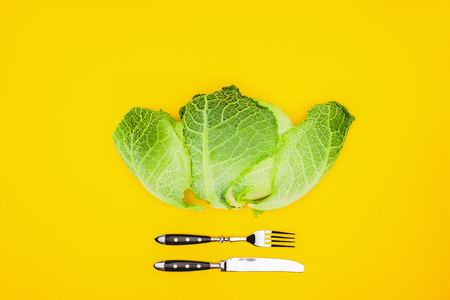 top view of fresh healthy cabbage and fork with knife isolated on yellow Foto de archivo