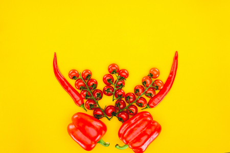 top view of fresh red peppers and cherry tomatoes isolated on yellow