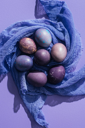top view of traditional painted eggs on gauze, on purple