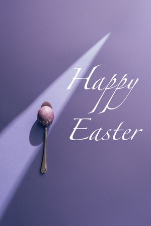painted egg in spoon on purple background with Happy Easter lettering Stok Fotoğraf - 96803347