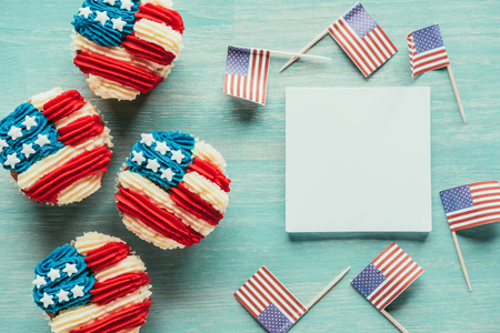 flat lay with arranged cupcakes and american flags on wooden tabletop Stock Photo