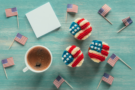 flat lay with arranged cupcakes, cup of coffee and american flags on wooden tabletop