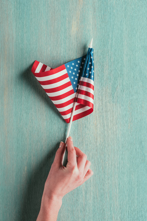 partial view of woman holding american flag in hand on blue wooden tabletop