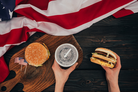 partial view of woman holding burger and soda drink, presidents day celebration concept Stock Photo