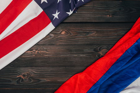 top view of american and russian flags on dark wooden tabletop Stock Photo