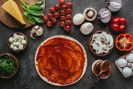 top view of uncooked pizza dough with sauce and vegetables on concrete table