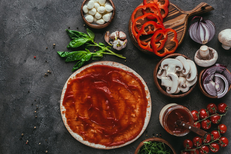 top view of raw pizza dough with sauce and vegetables on concrete table