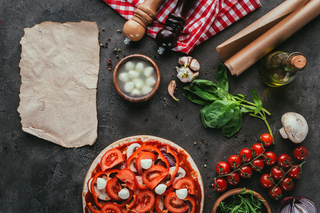 top view of uncooked pizza with ingredients and blank paper on concrete table