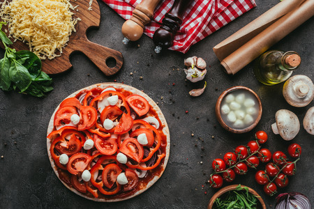 top view of uncooked pizza with ingredients on concrete table Stock Photo