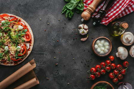 top view of uncooked pizza with ingredients on concrete table Imagens
