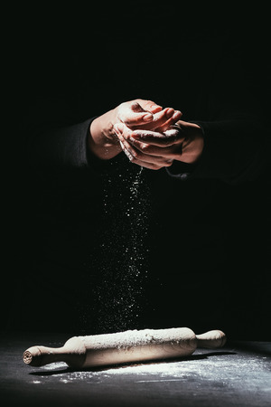 cropped shot of chef with hands covered in flour and rolling pin on table