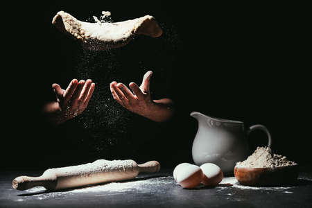cropped shot of chef throwing up dough for pizza on black Standard-Bild