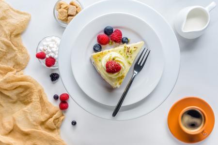 Draufsicht des Stückes Kuchens mit Beeren auf weißer Tabelle