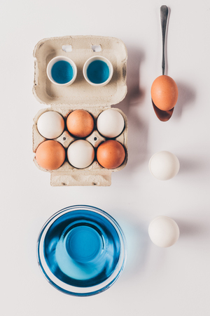 top view of glass with blue paint and different chicken eggs on white surface